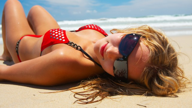 Young girl in red bikini is lying on white sand beach
