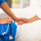 medical doctor holding senior patient's hands and comforting her