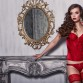 Beautiful alluring young woman in red sexy lingerie posing in antique interior