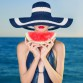 Young stylish lady in a hat at sea with watermelon