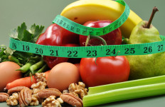 Group of wholesome, organic food, including pear, apple, tomato, eggs, nuts, pecans, walnuts, carrot, banana, and apple, for a healthy diet or slimming New Year resolution.