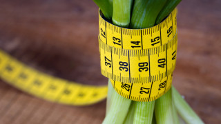 Green onions with yellow measurement tape on rustic wooden background; weight loss and diet concept