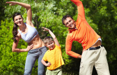 Portrait of family of three doing physical exercise in park