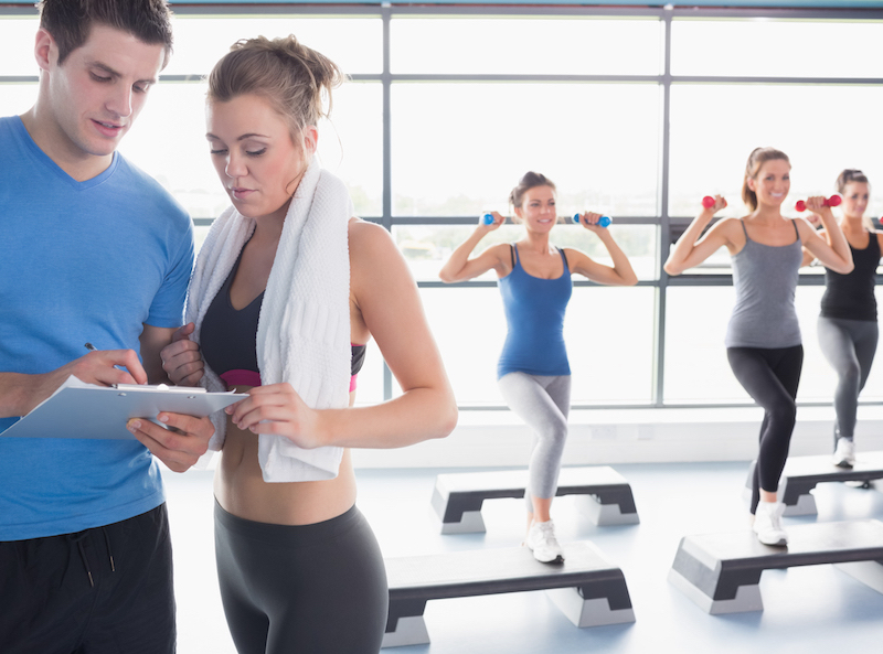 Women doing aerobics while trainer talking to woman in gym