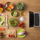 Online recipes concept with fresh vegetables, food ingredients and laptop on the right, top view