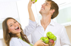 Happy Couple Eating fresh fruits.Having fun on a kitchen.Dieting concept.Healthy eating