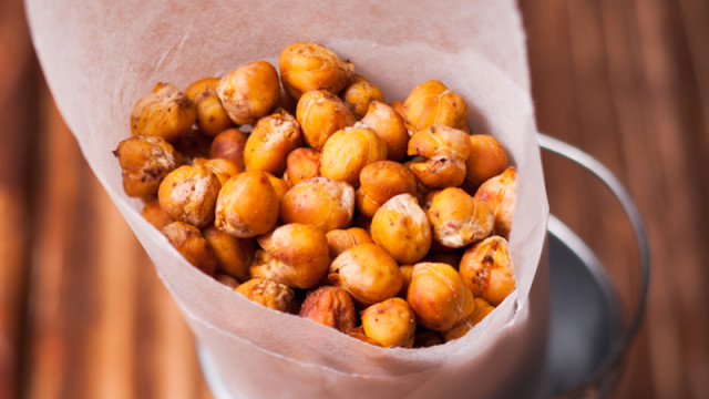 Spicy baked chickpeas in a metal pail on the wooden background