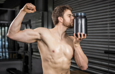 Shirtless man showing biceps and kissing can at the crossfit gym