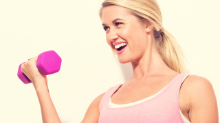 Happy young woman working out with dumbbell