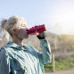 Blonde girl drinking water during morning jogging